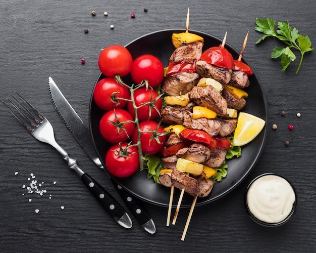 Вид сверху на тарелку с вкусным кебабом и помидорами Бесплатные Фотографии