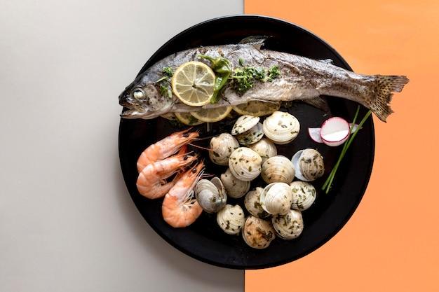 魚とアサリのプレートのトップビュー 無料写真