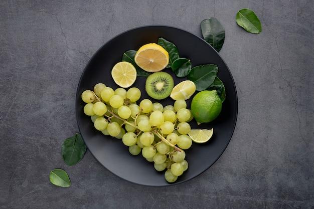 Вид сверху тарелка с виноградом и киви Бесплатные Фотографии