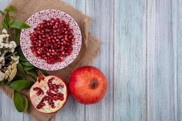 Вид сверху ягод граната в миске с целыми и половиной с цветами на деревянной поверхности Бесплатные Фотографии