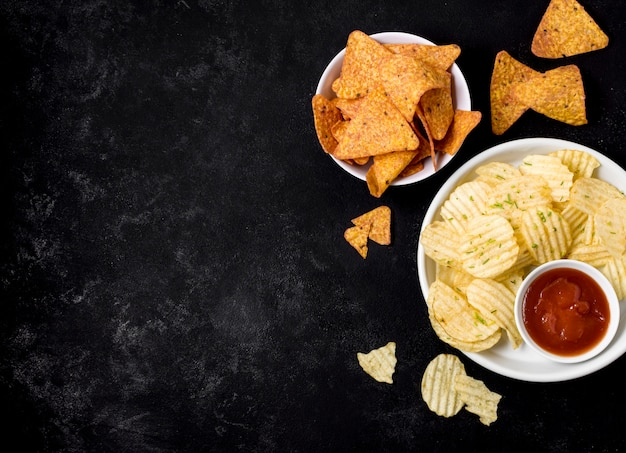Вид сверху картофельные чипсы и начо чипсы с кетчупом Бесплатные Фотографии