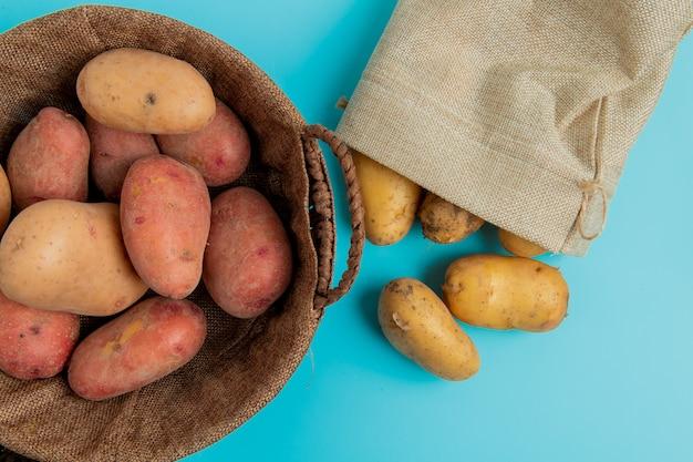 バスケットのジャガイモと青の袋からこぼれる他のものの平面図 無料写真
