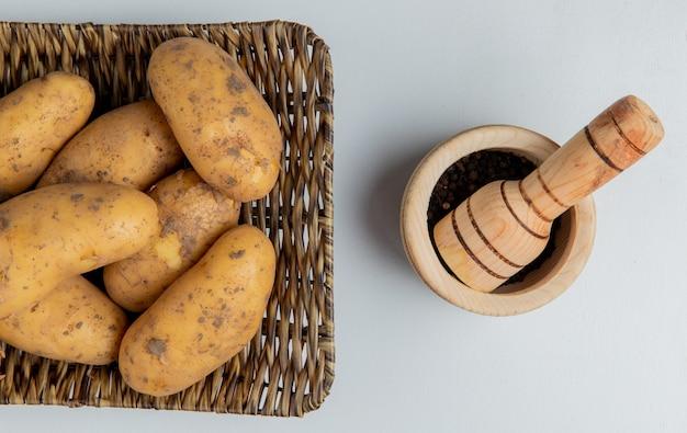 Вид сверху картофеля в корзине и семена черного перца в чесночной дробилке на белом Бесплатные Фотографии