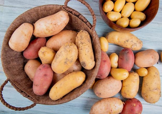 Вид сверху картофеля в корзине с новыми в миске и других разных видов на деревянной поверхности Бесплатные Фотографии