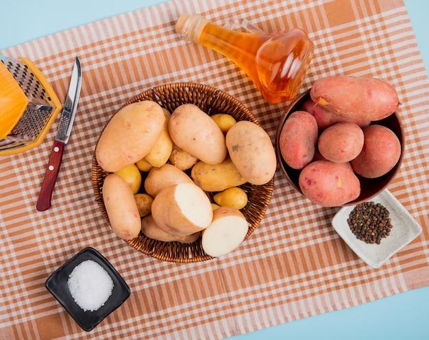 格子縞の布と青色の背景に塩黒コショウおろし金ナイフバターをボウルにジャガイモの平面図 無料写真