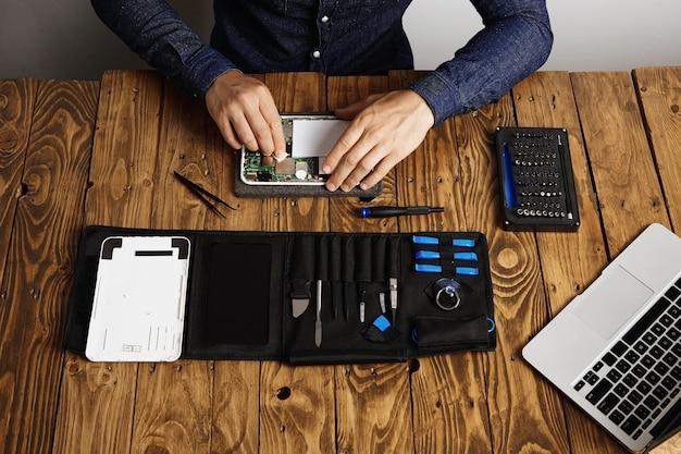 Вид сверху профессионального чистого электронного устройства на деревянном столе в его лаборатории рядом с его инструментами перед разборкой Бесплатные Фотографии