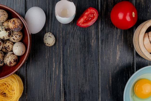コピースペースを持つ木製の背景に卵白と卵黄とトマトの木製ボウルにウズラの卵のトップビュー 無料写真