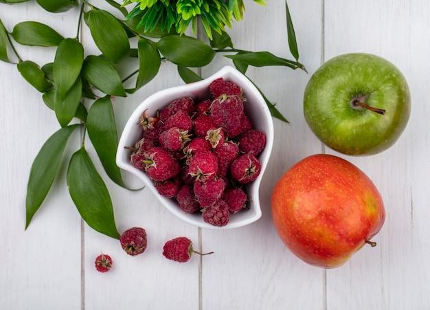 Вид сверху малины в миске с цветными яблоками и веткой на белой поверхности Бесплатные Фотографии