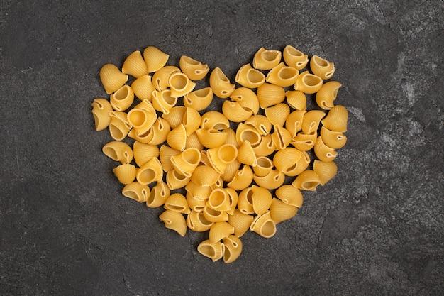 Вид сверху сырой итальянской пасты в форме сердца на темной поверхности Бесплатные Фотографии