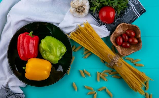ターコイズブルーの表面にベル色のピーマントマトとニンニクの生スパゲッティのトップビュー 無料写真