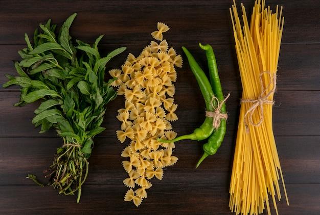 木製の表面に生パスタチリペッパーとミントの束のスパゲッティのトップビュー 無料写真