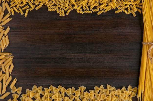 木製の表面に生パスタのスパゲッティのトップビュー 無料写真