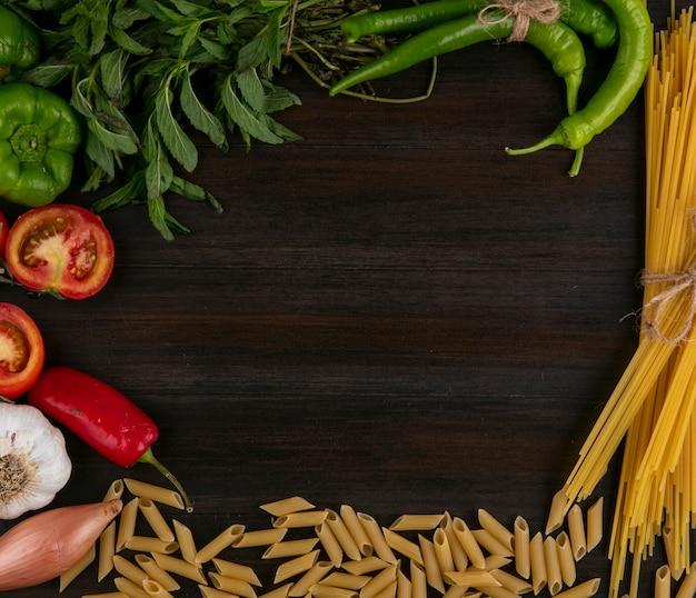 木製の表面に生パスタトマトピーマンとミントとニンニクのスパゲッティのトップビュー 無料写真