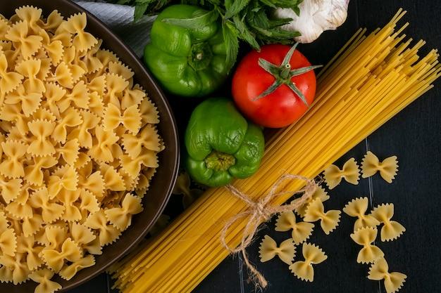 黒い表面にトマトニンニクとピーマンのボウルに生パスタと生スパゲッティのトップビュー 無料写真