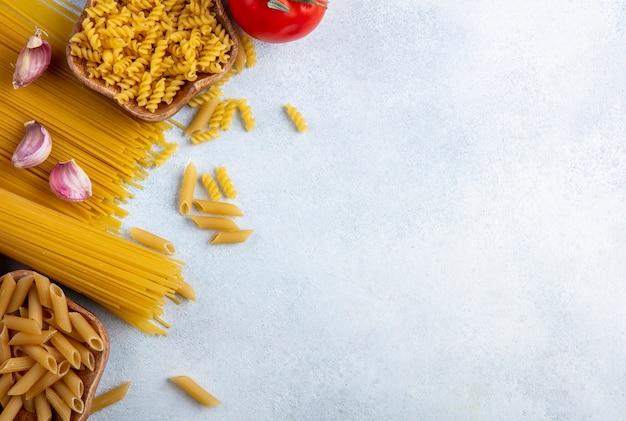 灰色の表面にニンニクとトマトのボウルに生パスタと生スパゲッティのトップビュー 無料写真