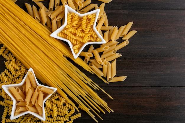 木製の表面に星型受け皿の生パスタと生スパゲッティのトップビュー 無料写真