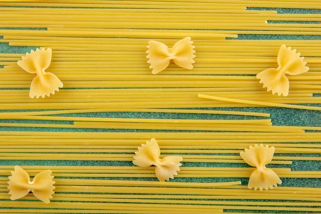 緑の表面に生パスタの生スパゲッティのトップビュー 無料写真