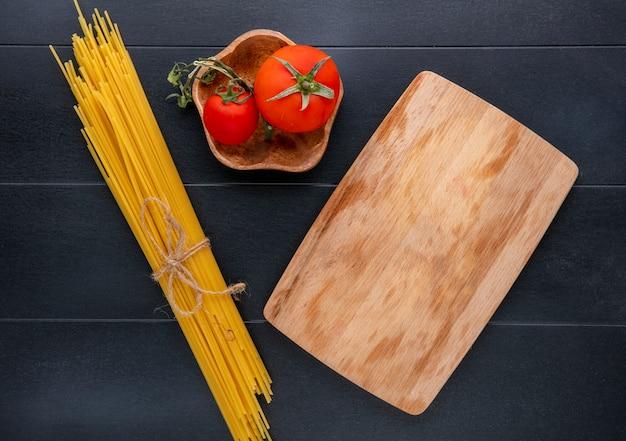 黒い表面にトマトと黒板の生スパゲッティのトップビュー 無料写真
