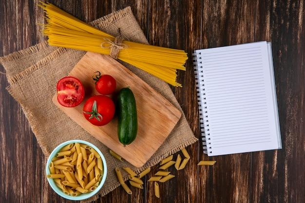 木製の表面にベージュのナプキンにノートとまな板の上のトマトとキュウリの生スパゲッティのトップビュー 無料写真