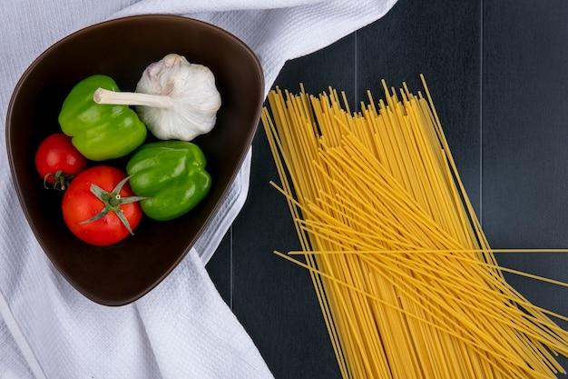 黒い表面に白いタオルの上にボウルにトマトニンニクとピーマンの生スパゲッティのトップビュー 無料写真