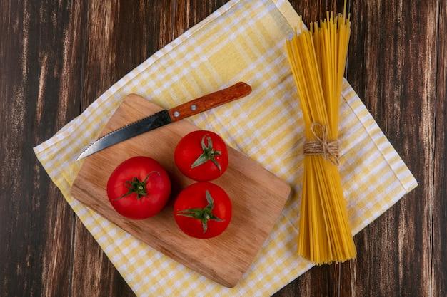 木製の表面に黄色の市松模様のタオルの上にナイフでまな板の上のトマトの生スパゲッティのトップビュー 無料写真