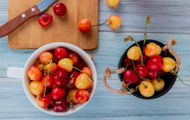 素朴な木の上のバケツで赤と黄色の熟したチェリーとボウルでレーニアチェリーのトップビュー 無料写真