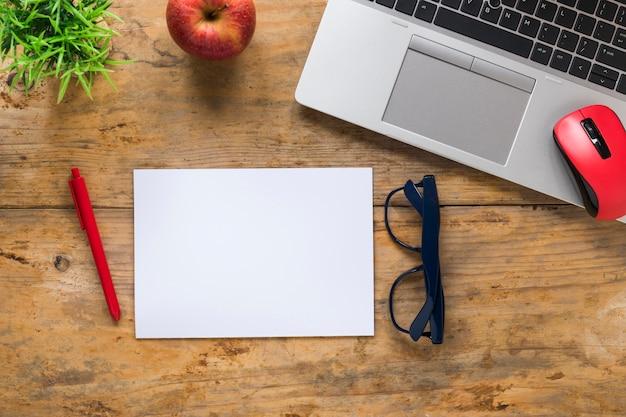 赤いリンゴの平面図。マウス;ノートパソコンペン;眼鏡と木製の机の上の空白のホワイトペーパー 無料写真
