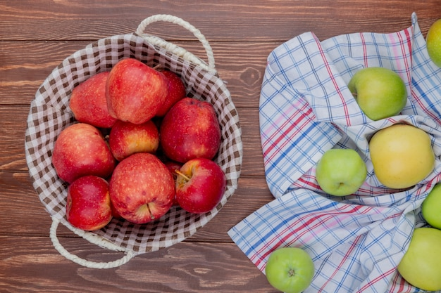 Вид сверху красных яблок в корзине с зелеными на клетчатой ткани на деревянном фоне Бесплатные Фотографии
