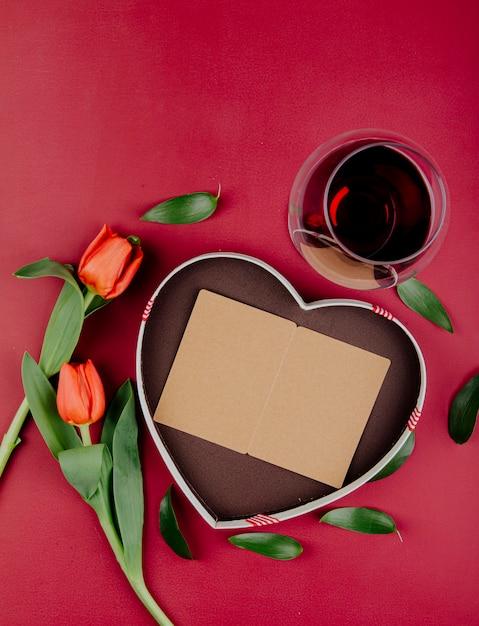 赤の背景にハート型のオープンポストカードと赤ワインのグラスのギフトボックスと赤い色のチューリップの花のトップビュー 無料写真