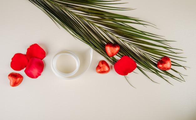 赤いバラの花びらのトップビュー、白いテーブルにリボンと赤い箔とヤシの葉に包まれたハート型のチョコレート菓子 無料写真