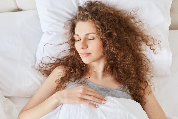 リラックスした巻き毛の女性の平面図はベッドで健康的な睡眠をとり、白いリネンの上に横たわり、夜は心地よい夢を楽しんでいます。 Premium写真