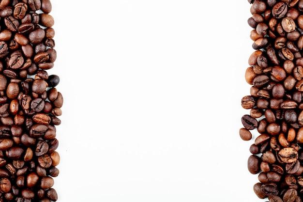 Вид сверху жареных кофейных зерен на белом фоне с копией пространства Бесплатные Фотографии