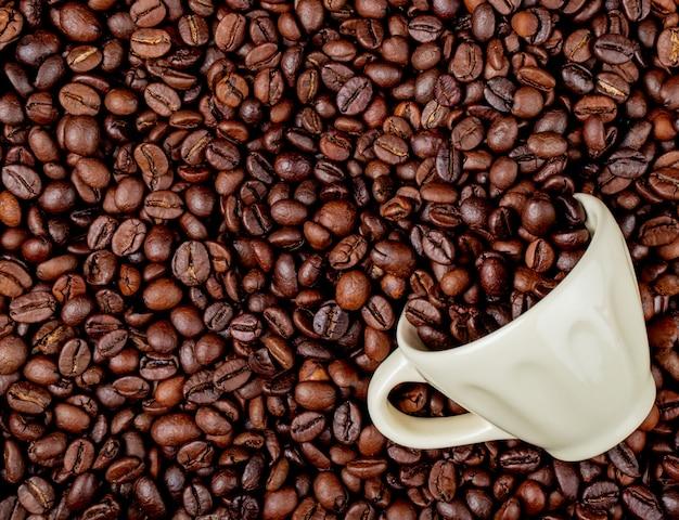 コーヒー豆の背景にセラミックカップから散乱ローストコーヒー豆のトップビュー 無料写真