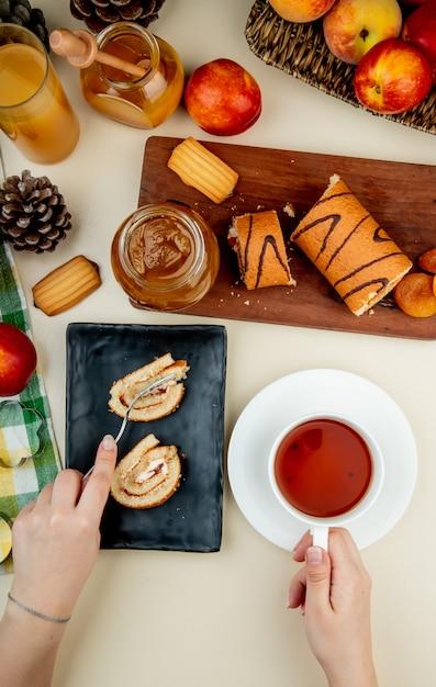 黒のトレイの上に敷設し、紅茶のカップと桃のジャムクッキーの新鮮な熟したネクタリンと白のジュースのガラスとガラスの瓶を保持しているロールケーキのトップビュー 無料写真