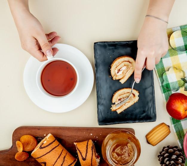 ブラックトレイの上に敷設し、紅茶のカップと白の桃ジャムクッキー新鮮な熟したネクタリンとクッキーカッターとガラスの瓶を保持しているロールケーキのトップビュー 無料写真