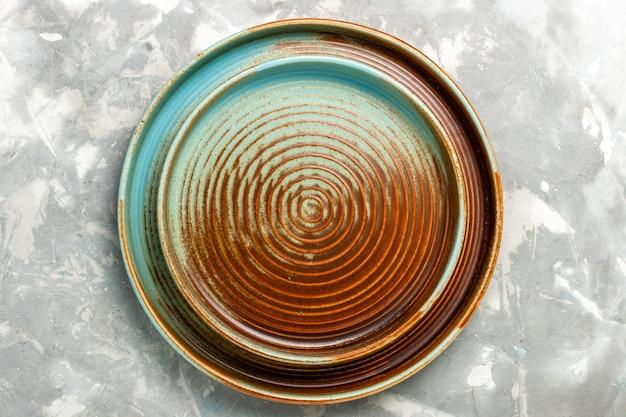 薄い灰色の表面で分離された空の丸い茶色の鍋の上面図 無料写真