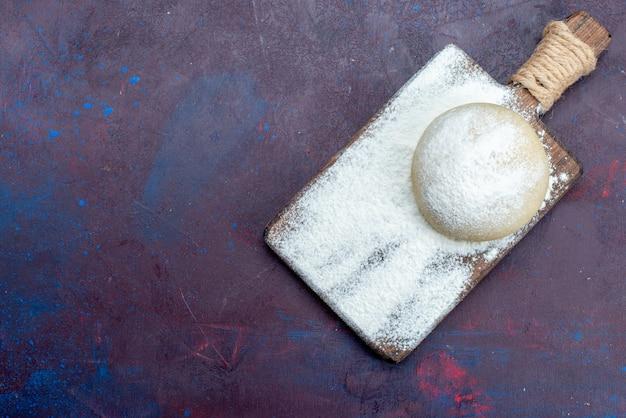 暗い表面に白い小麦粉が付いている丸い生地の上面図 無料写真