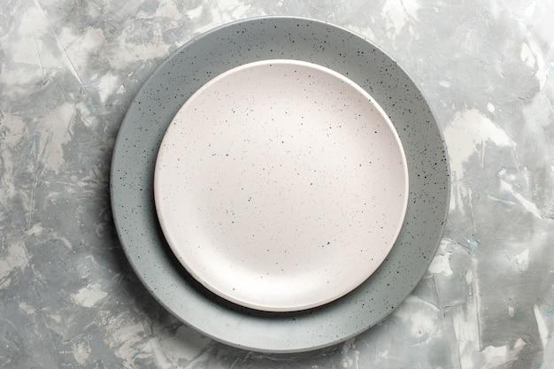 灰色の表面に白いプレートで着色された灰色の丸い空のプレートの上面図 無料写真