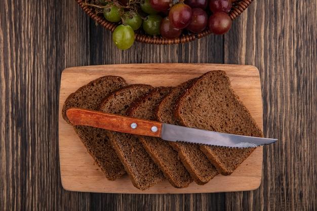 Вид сверху на ломтики ржаного хлеба и нож на разделочной доске с корзиной винограда на деревянном фоне Бесплатные Фотографии