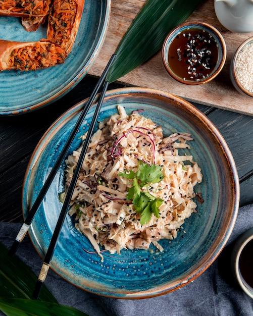 木の上に刻んだキャベツチキンと箸で皿に黒い種子のサラダのトップビュー 無料写真