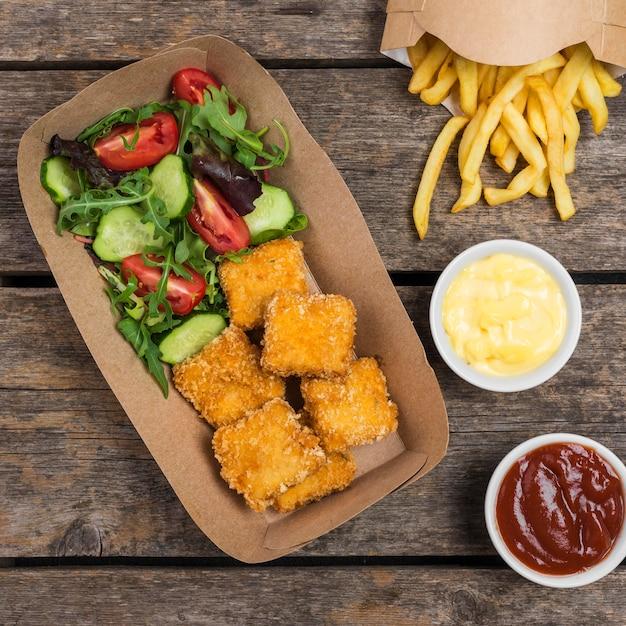 フライドポテトとフライドチキンのサラダのトップビュー 無料写真