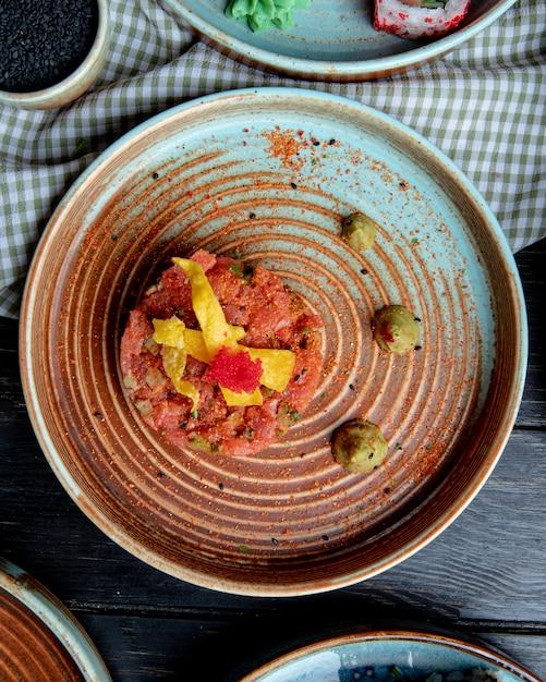 Вид сверху салат из лосося с авокадо и соусом васаби на тарелке на клетчатой ткани Бесплатные Фотографии