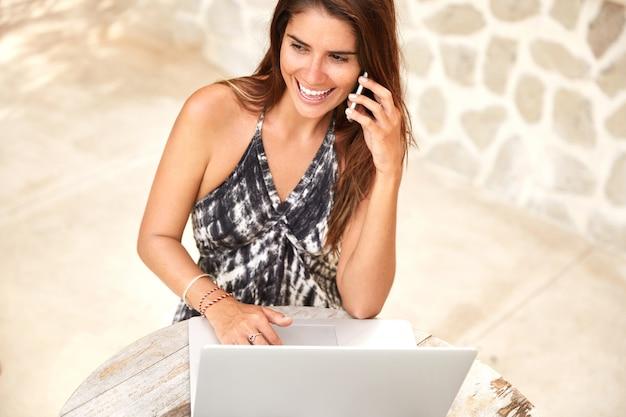 満足のいく女性モデルの上面図はカフェテリアで再現し、スマートフォンで親友と話をし、ワイヤレス高速インターネットに接続されたラップトップコンピューターでリモートで動作します。女性フリーランサー 無料写真