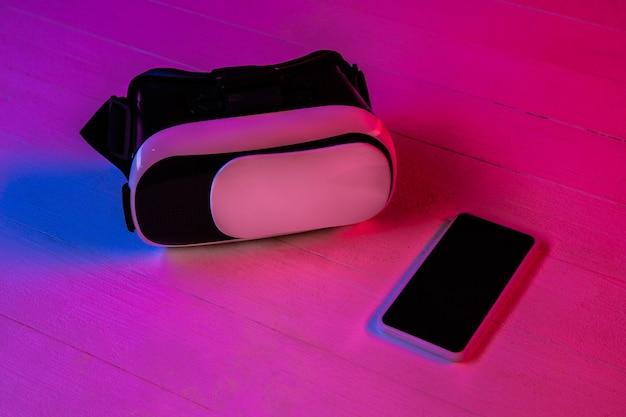 Вид сверху набора гаджетов в фиолетовом неоновом свете и розовом фоне. смартфон и vr-гарнитура. copyspace для вашей рекламы. техника, модерн, гаджеты. виртуальная реальность. Бесплатные Фотографии