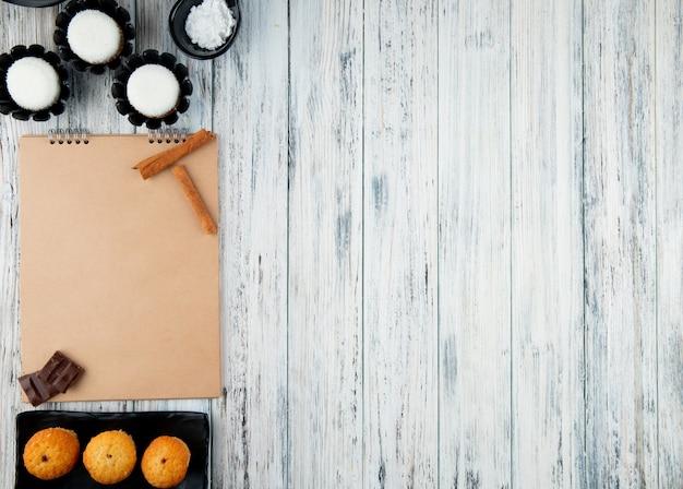 コピースペースと白い木製の背景にスケッチブックとティービスケットの盛り合わせのトップビュー 無料写真