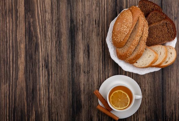 Вид сверху на нарезанный хлеб в виде засеянной коричневой ржи и белой ржи в тарелке и чашке горячего пунша с корицей на блюдце на деревянном фоне с копией пространства Бесплатные Фотографии