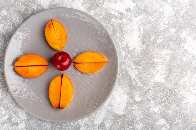 Вид сверху нарезанных свежих персиков внутри тарелки, выложенной на светло-белой поверхности Бесплатные Фотографии