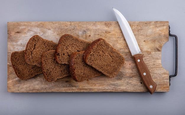 Вид сверху нарезанного ржаного хлеба и ножа на разделочной доске на сером фоне Бесплатные Фотографии