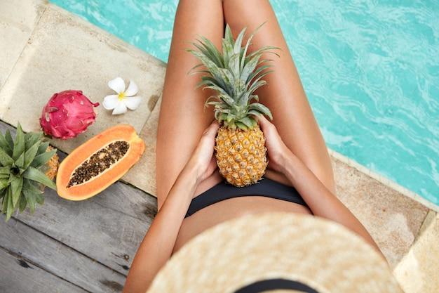日焼けした肌を持つスリムな女性の平面図、ホテルのプールの近くに座ってビーガンの健康的な食事を楽しみ、トロピカルフルーツを食べる、夏のプールパーティーがあります。女性はジューシーなエキゾチックな収量を食べる:パイナップルとパピア 無料写真