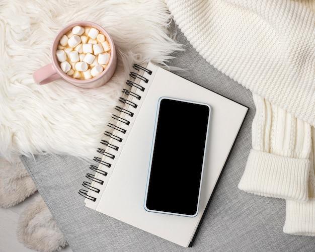 ホットココアのカップとスマートフォンとノートブックの上面図 無料写真